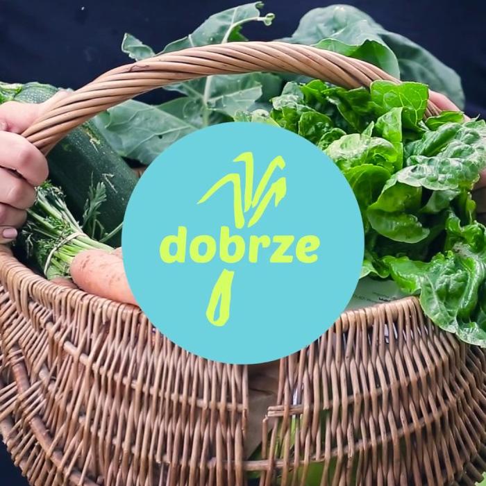 Brązowy, wiklinowy kosz zzielonymi warzywami wśrodku. Naśrodku niebieskie logo Kooperatywy Dobrze.