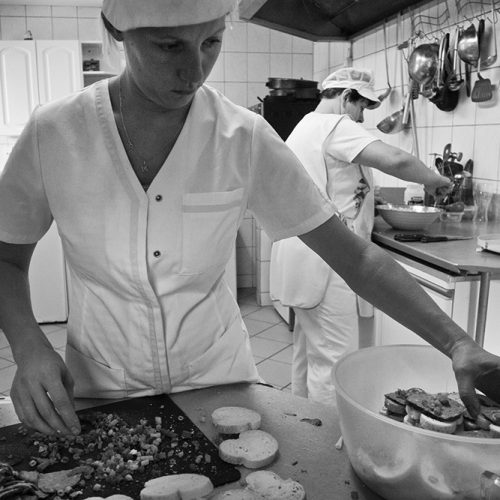 Czarno-biała fotografia. Dwie kobiety wbiałych fartuchach iczepkach gotują jedzenie wkuchni.